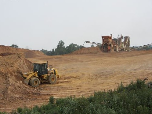 Front end loader getting raw material to load crusher